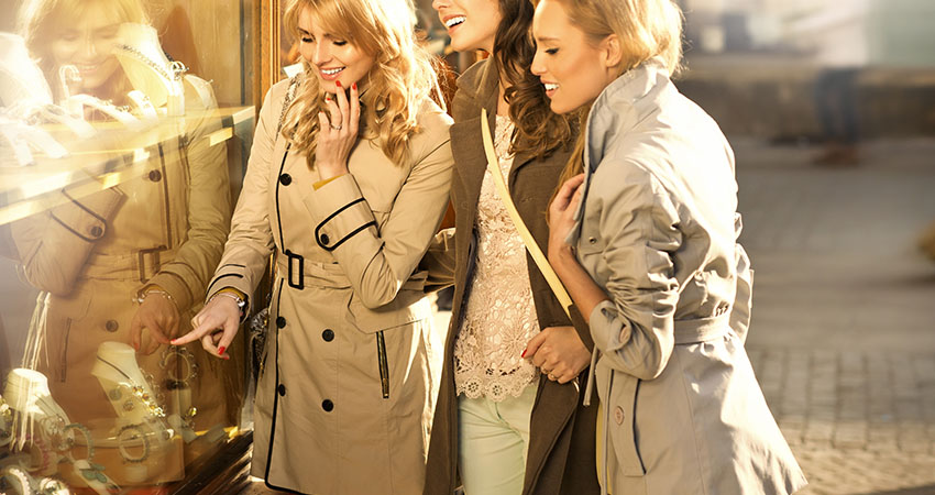 Three girlfriends looking at the shop window