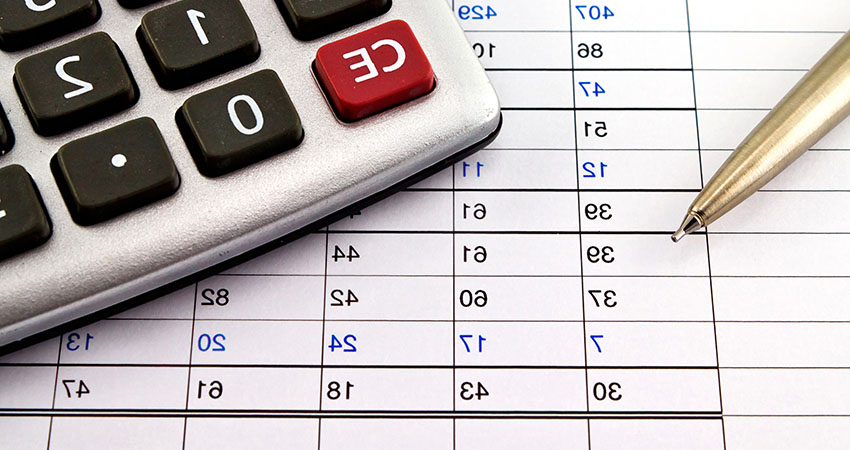 Financial reports with pen and calculator