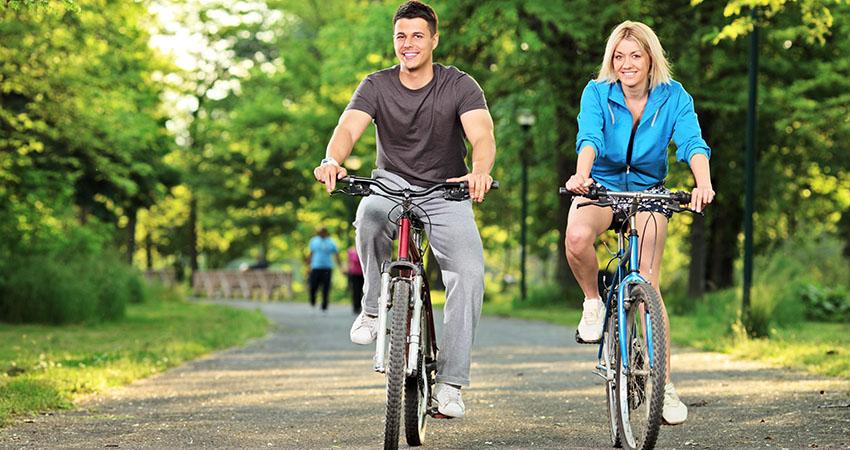 Happy couple biking in the park