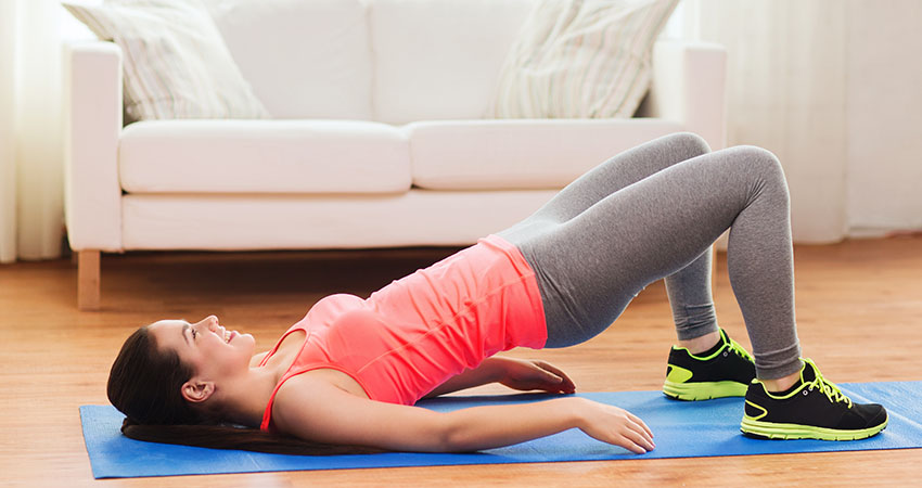 smiling girl doing exercise for legs and buttocks