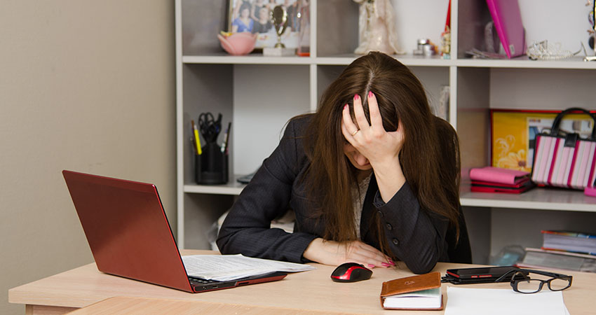 Girl in the office clutching her head