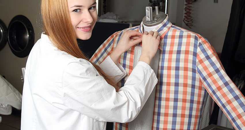 Woman in a dry cleaning on Ironing doll machine